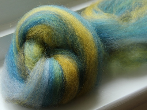 A stack of batts pulled into roving with thick stripes